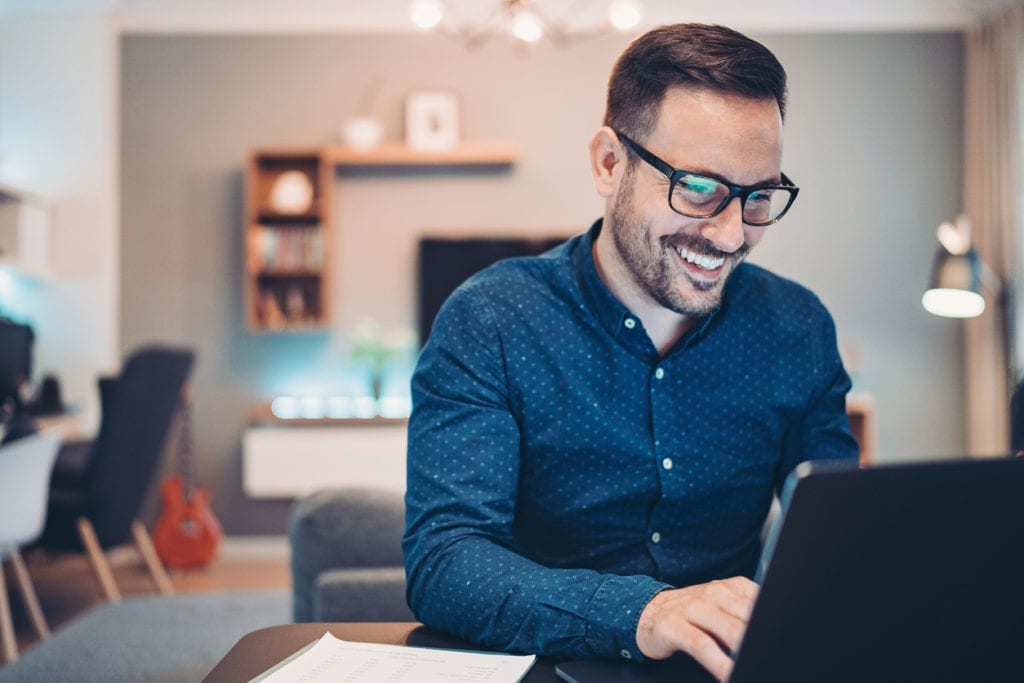 smiling-man-sitting-at-desk-at-home-with-open-laptop-and-living-room-behind-him