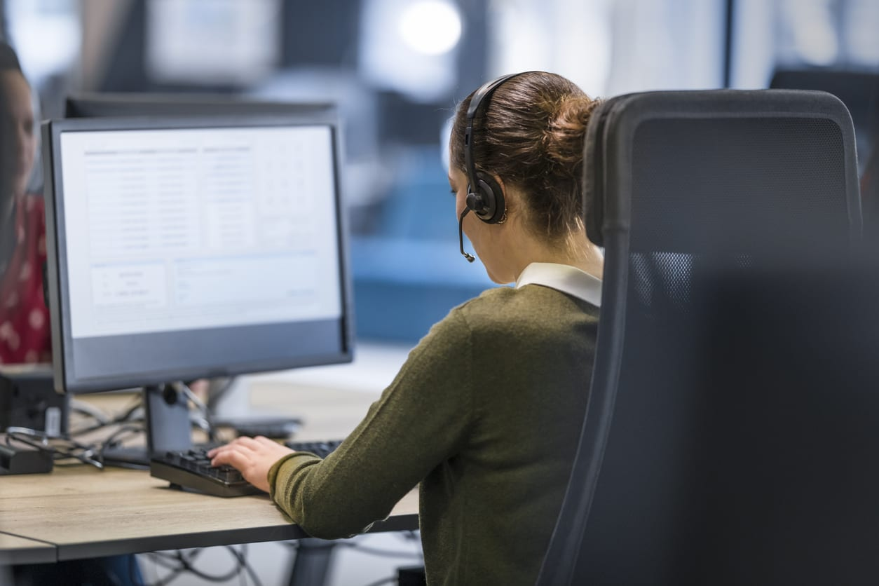 woman-wearing-headset-sitting-in-office-chair-at-desk-with-computer-monitor